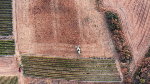 Aerial view in 4K followed by a tractor plowing a field