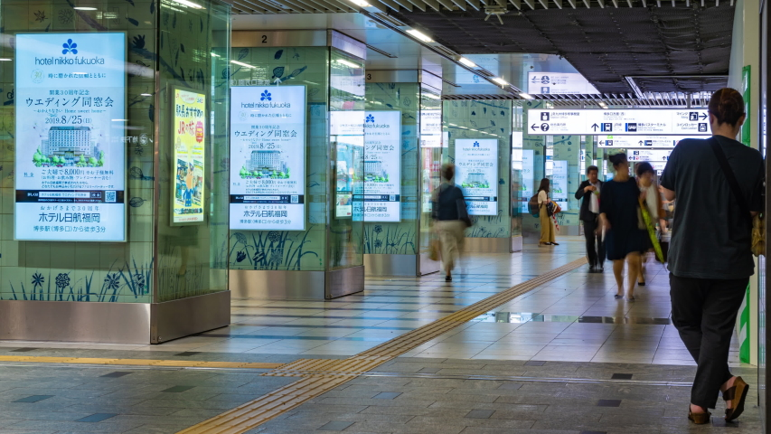 Fukuoka, Japan - 10 July 2019 - People walk along the train station hallway surrounded by various shops and advertisement signs in Fukuoka, Japan on July 10, 2019 #1036509527