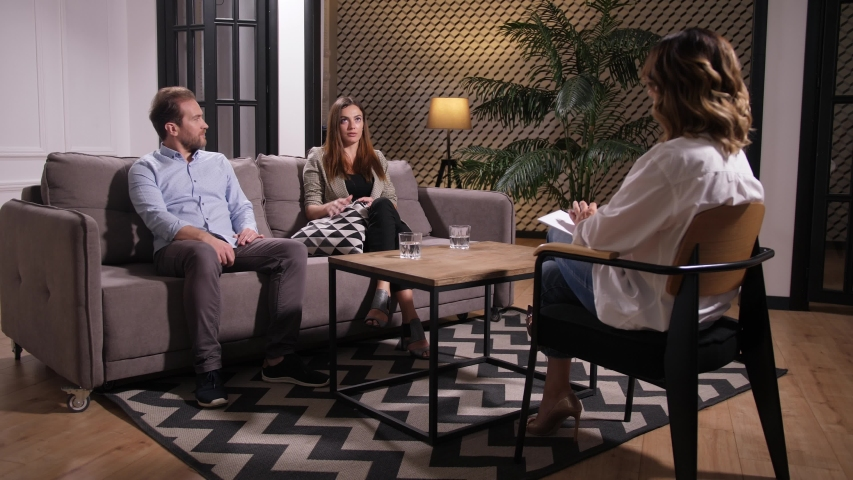 Adult couple sitting on sofa on appointment and discussing relationship problems with family counselor. Nervous wife drinking water while calm husband expressing his point of view on crisis situation | Shutterstock HD Video #1036597367