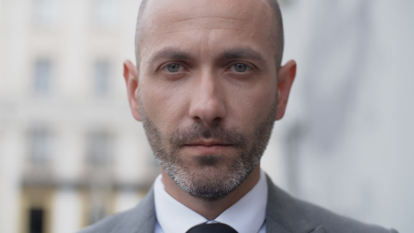 Close up attractive middle aged bearded man in business suit looking into camera seriously in the city outdoors. Portrait of handsome serious male businessman standing on office porch #1036604147