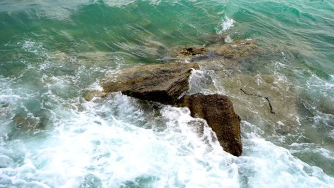 Nature background. Rough sea waves splash at rocky coast stones