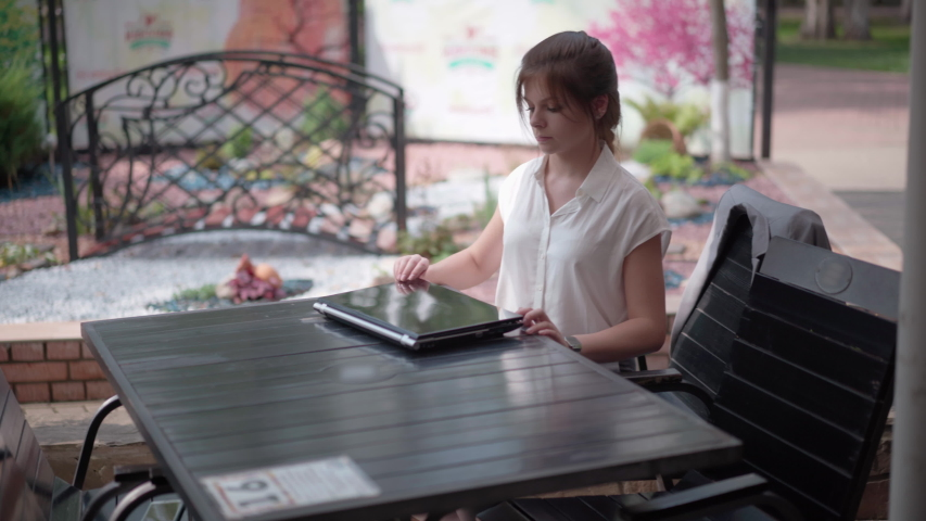 Young businesswoman in a street cafe is typing on a laptop. | Shutterstock HD Video #1036669187