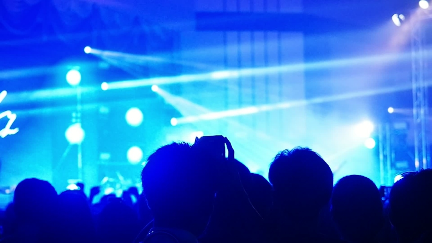 Some cheering fans take a photograph or video in a free live concert in music festival. This concert is free no charge and doesn't requires press credentials.