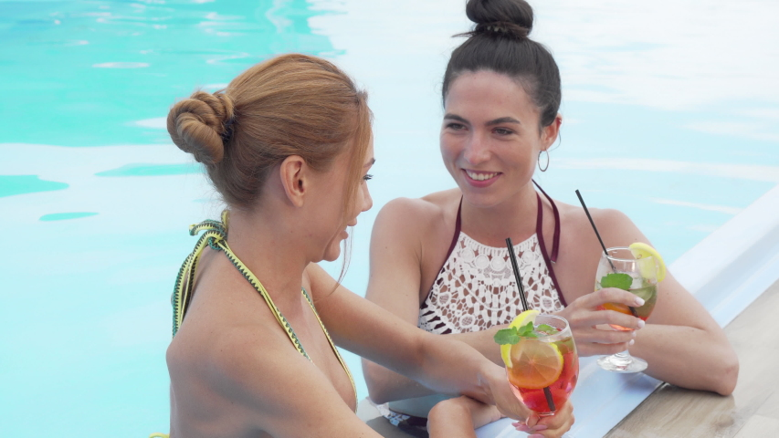Two gorgeous women talking and drinking cocktails at the swimming pool | Shutterstock HD Video #1036765127
