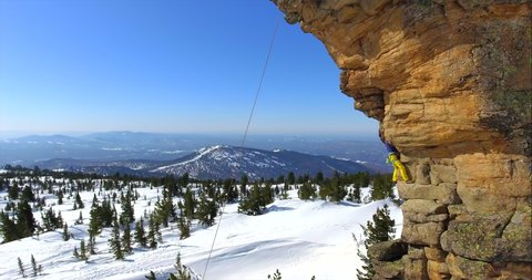 a climber climbs a steep rock in a bright suit on a safety rope. climber conquers beautiful cliffs in winter in a mountain valley. Rock climbing lessons. Rocky cliff winter. Drone footage. Aerial shot