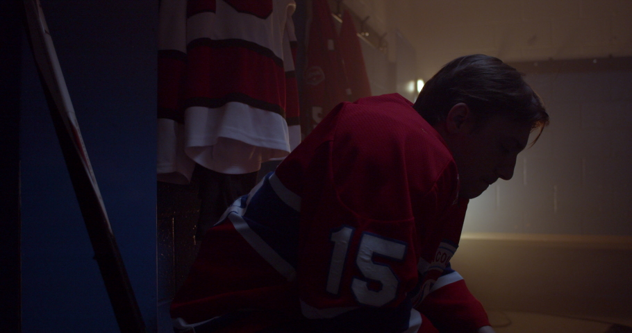 Hockey player sits in dramatically lit changeroom focused and determined to win a crucial game in series | Shutterstock HD Video #1036851257
