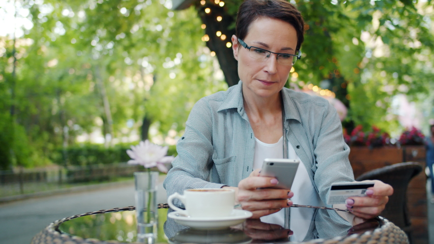 Mature businesswoman is making online payment with credit card using smartphone in outdoor cafe touching screen smiling. Lifestyle and finance concept. | Shutterstock HD Video #1036914617