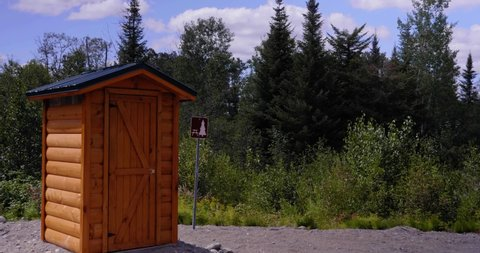 Amos, Québec/Canada 08-24-2019: Small chemical toilet built in round wood on a walking trail