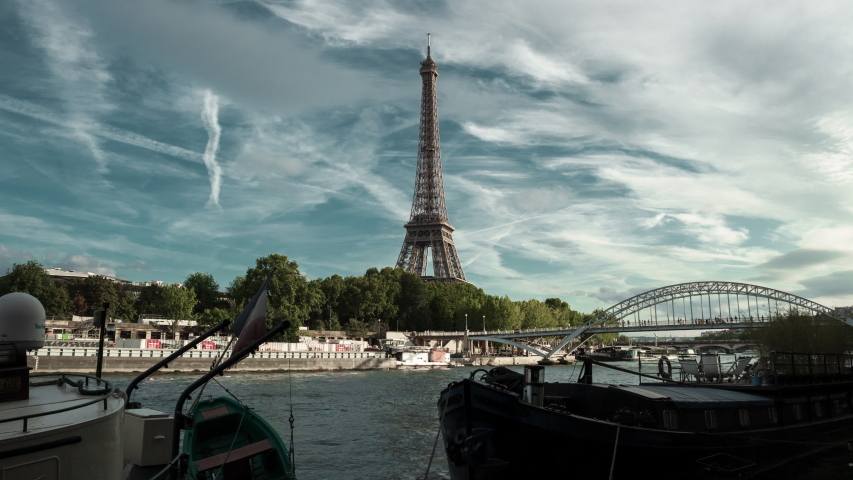 Eiffel Tower and river boats on zooming  time lapse during rush hours in Paris, France. Summer cityscape, city life, vacation and touristic places in Europe. | Shutterstock HD Video #1036969007