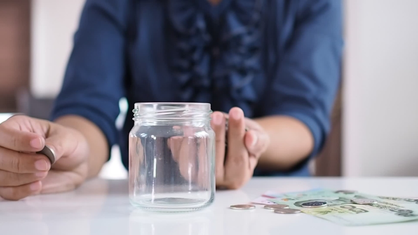 Young asian woman counting coins in glass bottle and plan future finances with savings By collecting thai money banknote and coins. | Shutterstock HD Video #1036972097