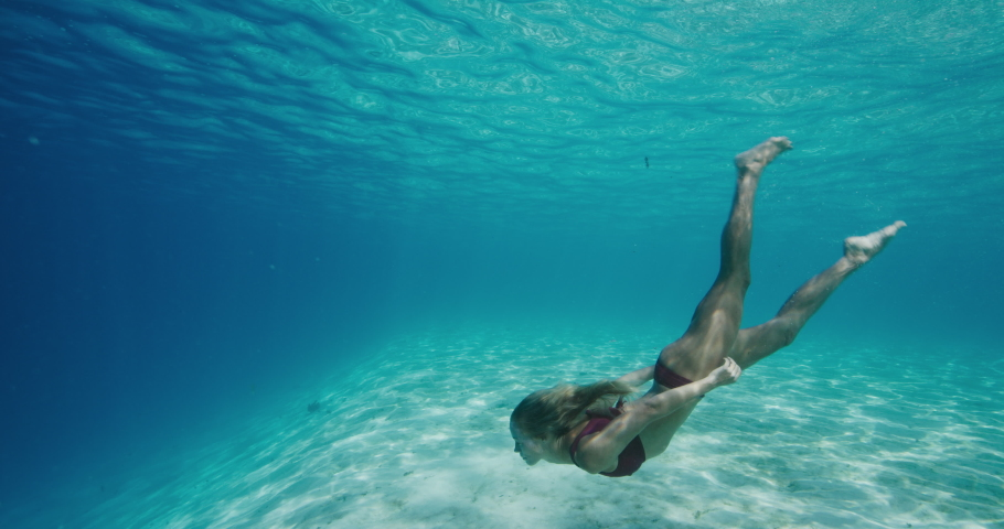 Beautiful woman swimming underwater gracefully in perfect blue ocean water and coming up to the surface #1036993847