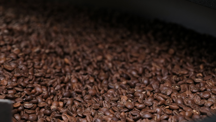Freshly roasted coffee beans on a cooling tray, being mixed by a rotating mechanical arm, then being emptied. Close-up Shot of Mixing dark roasted coffee beans in a cooler. | Shutterstock HD Video #1037010587