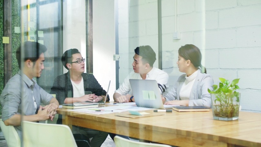 Group of young asian entrepreneurs meeting in office discussing business plan | Shutterstock HD Video #1037075417