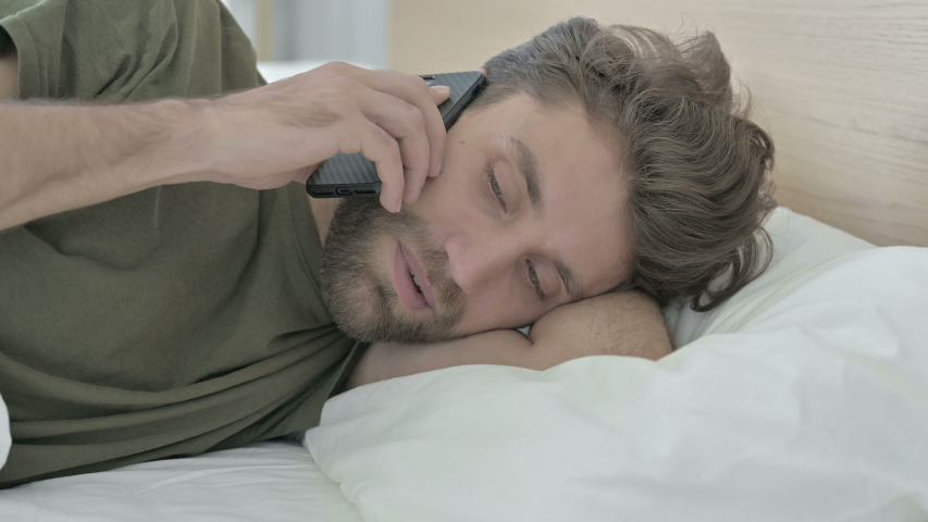Close-up of Young Man talking on Cellphone in Bed   Shutterstock HD Video #1037085977