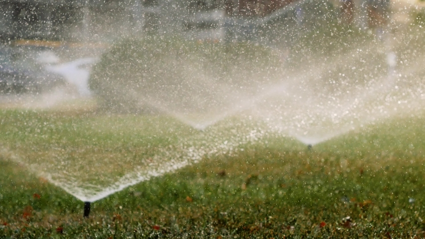Green field is watered with garden sprinklers. Water spraying out of sprinkler on the green lawn 4k | Shutterstock HD Video #1037162357