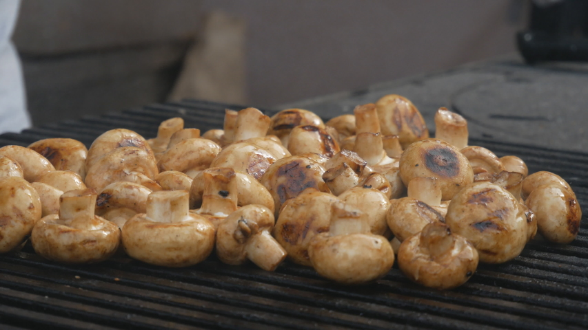 Chef's hands cooks mushrooms on the grill. Delicious, wholesome grilled food. Diet vegan barbecue. barbecue party | Shutterstock HD Video #1037174567