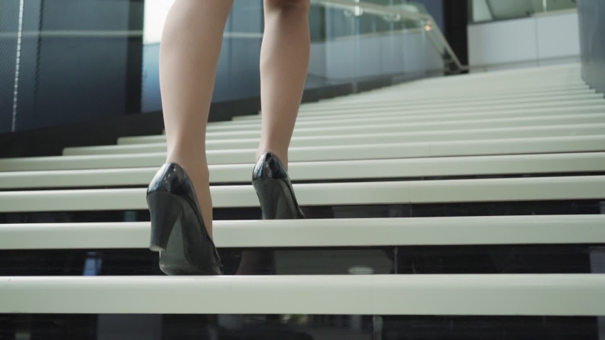 Rear view closeup follow shot of unrecognizable businesswoman in high heels shoes walking upstairs in office building in slow motion | Shutterstock HD Video #1037183657