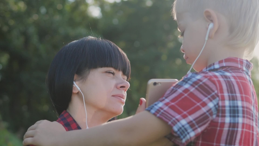 Happy family funny nature slow motion video teamwork outdoors. Mom and son listen to music on a smartphone in the same headphones for two . happy family mother woman and son little boy spend   Shutterstock HD Video #1037217917