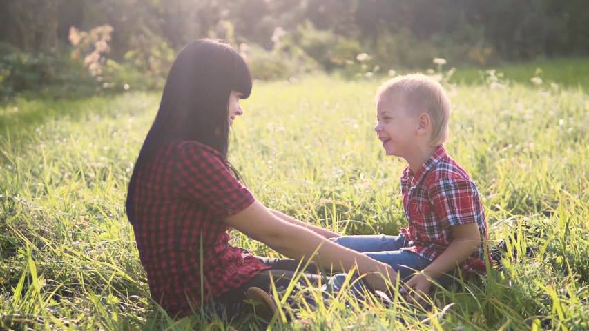 Happy family mother's day funny the nature slow motion video teamwork outdoors. mom girl holds son boy in sitting on the grass sunlight cute video care. mother and son sitting on the grass laughing   Shutterstock HD Video #1037218007