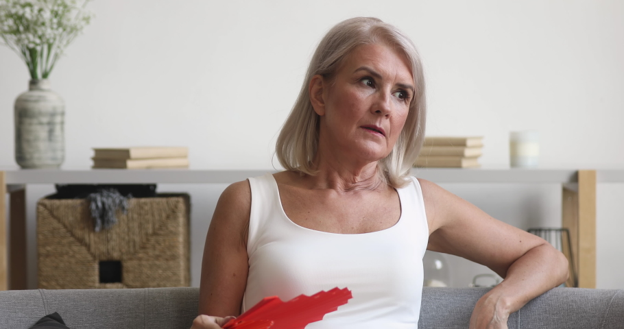 Stressed sweaty old woman breath hold wave red fan suffer complain on heat at home, overheated annoyed mature lady sweating feel uncomfortable hot in summer weather problem without air conditioner | Shutterstock HD Video #1037252567