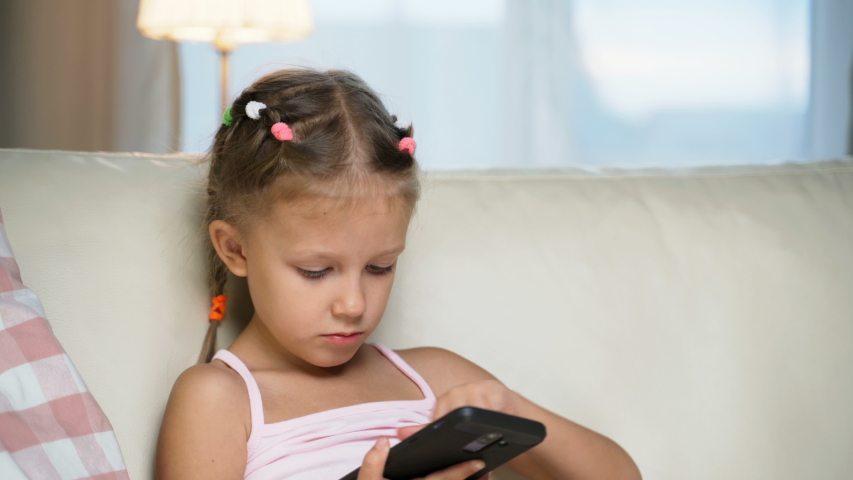 Little Girl Child Home On Sofa Playing On Smartphone   Shutterstock HD Video #1037314487