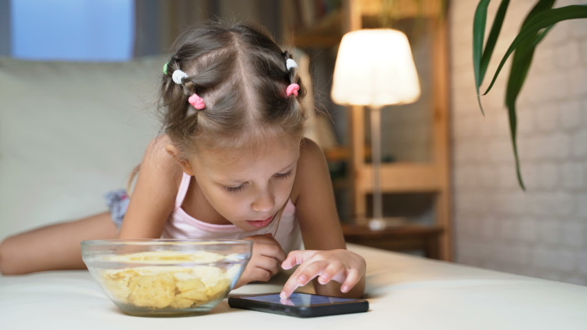 Little Girl Child Home On Sofa Playing On Smartphone   Shutterstock HD Video #1037314547