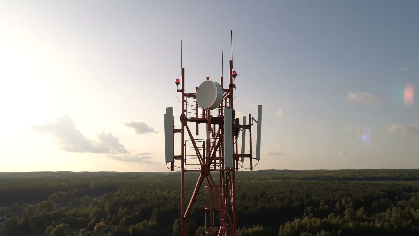 Closeup aerial shot around of telecommunication tower in a rural location. Telecom tower antennas and satellite transmits the signals of cellular 5g 4g mobile signals to the consumers and smartphones. | Shutterstock HD Video #1037383007