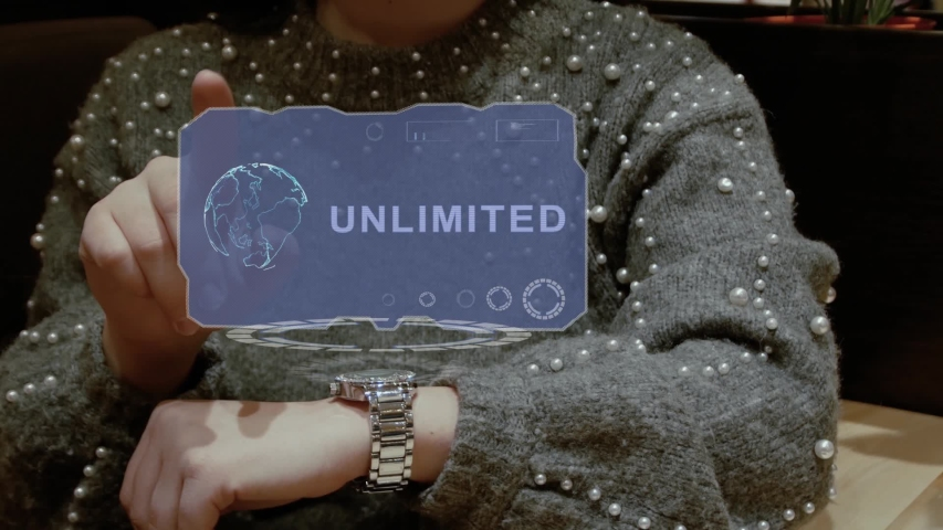 Unrecognizable woman working with HUD hologram of a smart watch with text Unlimited. Female hands with future holographic technology in wrist watches | Shutterstock HD Video #1037442167