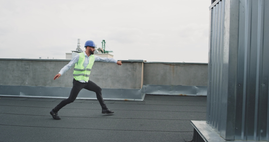 Very charismatic young architect dancing excited in the top of construction site he enjoying the moment on the rooftop of building | Shutterstock HD Video #1037504417