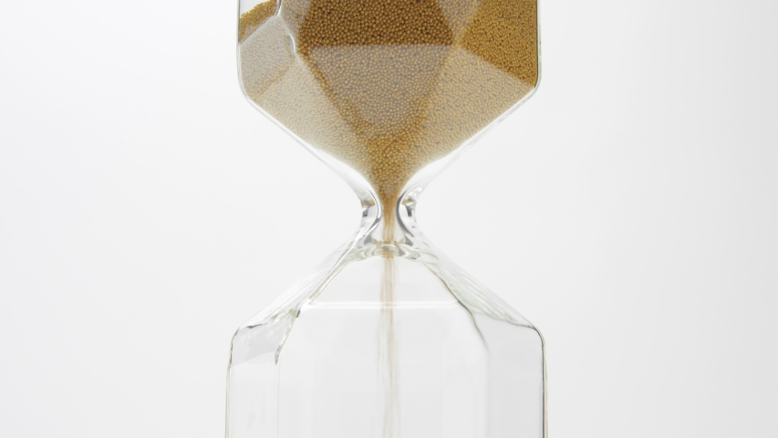 Closeup of a glass sand clock on white with golden balls instead of sand falling | Shutterstock HD Video #1037505737