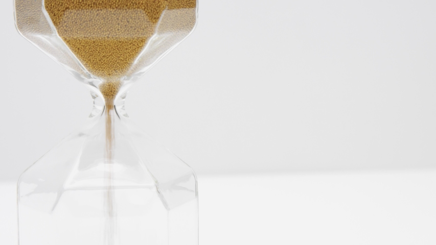 Closeup of a glass sand clock on white with golden balls instead of sand falling. Time concept footage | Shutterstock HD Video #1037505767