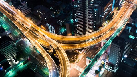Multi-hour aerial view time-lapse of a massive highway intersection at night in Shinjuku, Tokyo, Japan.