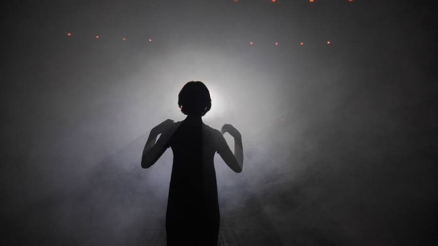 Dark silhouette of slim girl with short hair mimes touching shoulders at bright lights in smoke in studio slow motion | Shutterstock HD Video #1037851577