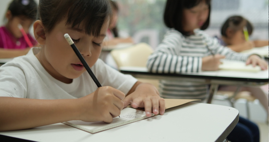 Asian children study and writing the classroom at school together. Concept of education.   Shutterstock HD Video #1037924447