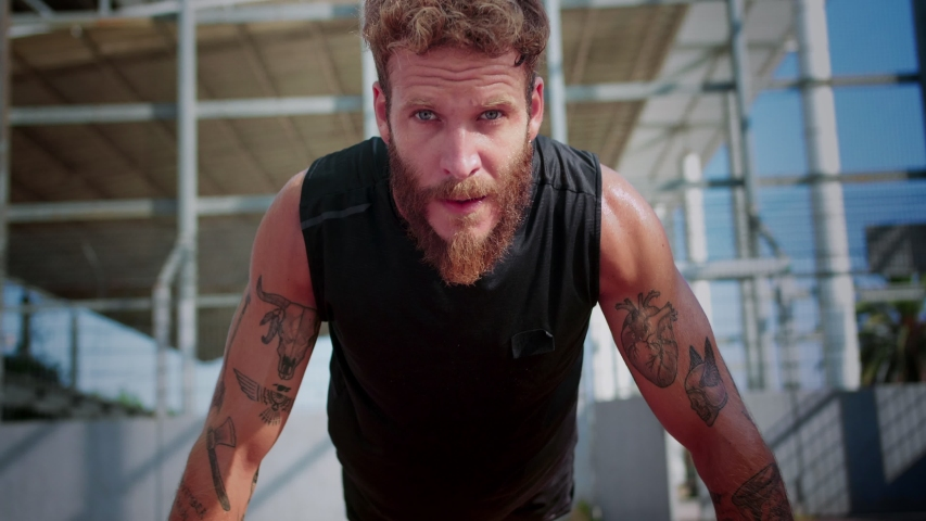 Close up of concentrated bearded man doing push-ups with tattooed hands at sport ground, looking straight to camera effort motivation force intense endurance of male dressed in black sportswear | Shutterstock HD Video #1037946797