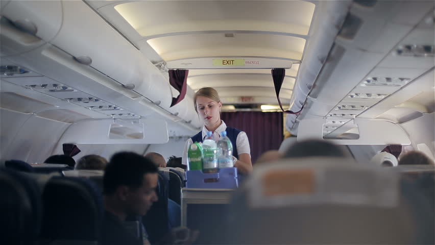 """TURKEY, SIDE - JUNE 1, 2015: Air hostess of """"Ural airlines"""" serves handing out food to passengers"""