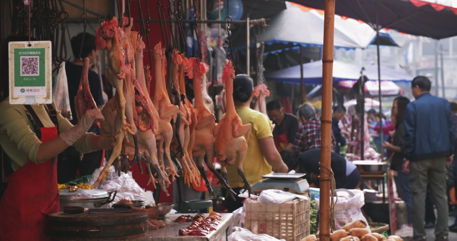 Chengdu.Sichuan/China-September 27th 2019: people shopping for vegetables meat in the fresh market, old style open outdoor food market street young female vendor busy on chicken poultry stall #1038063287