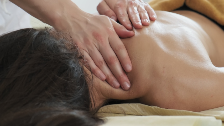 Young woman having massage in spa salon. Close-up of woman relaxing during back massage lying on massage table in slow motion | Shutterstock HD Video #1038075587