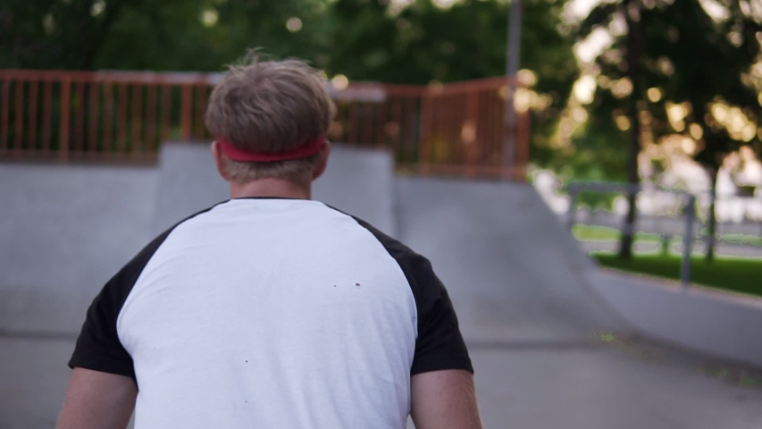 Blonde young guy in in wide black pants and a red bandage on his hair makes a beautiful somersault running on a skate ramp in the park. Footage from the back | Shutterstock HD Video #1038303377