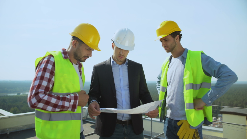 Young male boss in safety helmet discussing construction plan with workers #1038444257