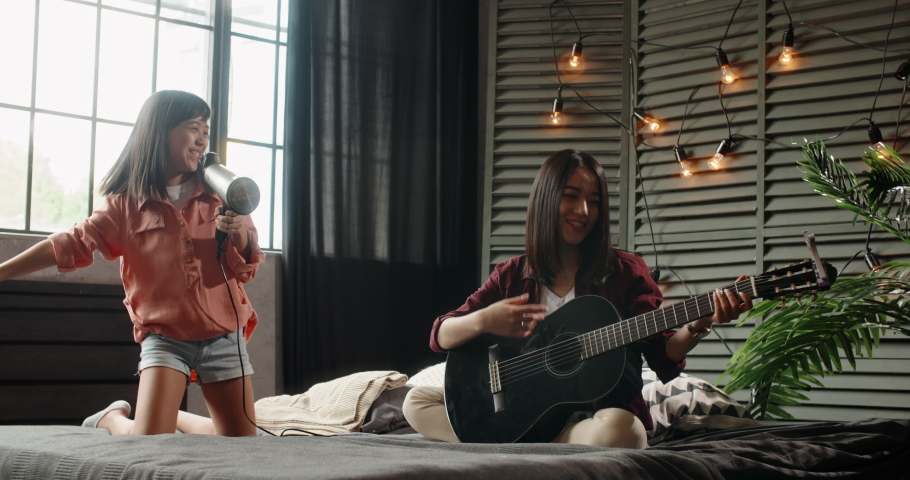 Two asian sisters sitting on bed, elder playing guitar while little kid is singing into hairdryer. Friends having fun spending time together at home - recreational pursuit, family time 4k   Shutterstock HD Video #1038540167