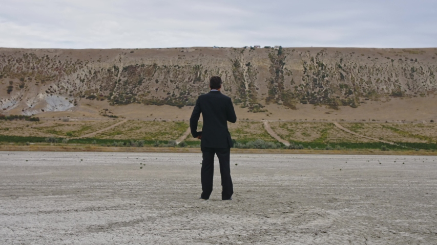 A man in a business suit stands at the bottom of a dried-up lake and rummaging through his pockets | Shutterstock HD Video #1038725297