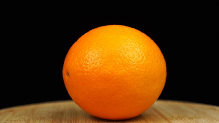 Orange on a wooden board, rotation 360 degrees. Black background.   Shutterstock HD Video #1038758537