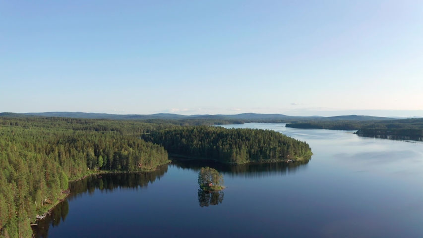 Drone shot of crystal clear lake in Sweden inland surrounded by deep forest landscape | Shutterstock HD Video #1038782567