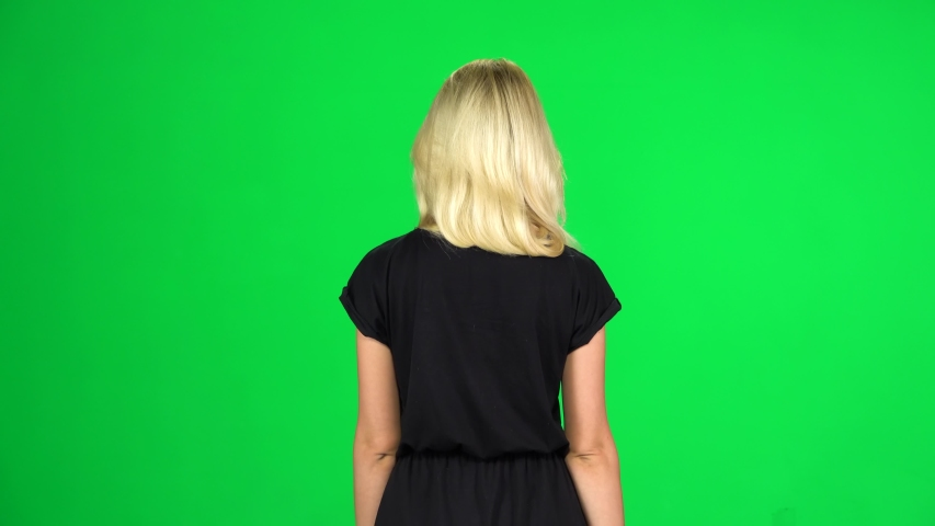 Back view of blonde girl is walking. Female dressed in black dress isolated on green screen at studio.   Shutterstock HD Video #1038784457