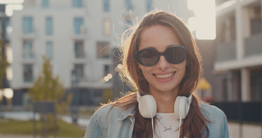 Portrait shot of the young sylish and pretty Caucasian woman in black sunglasses and with big headphones on her neck smiling cheerfully to the camera at the street. Close up. | Shutterstock HD Video #1038821747
