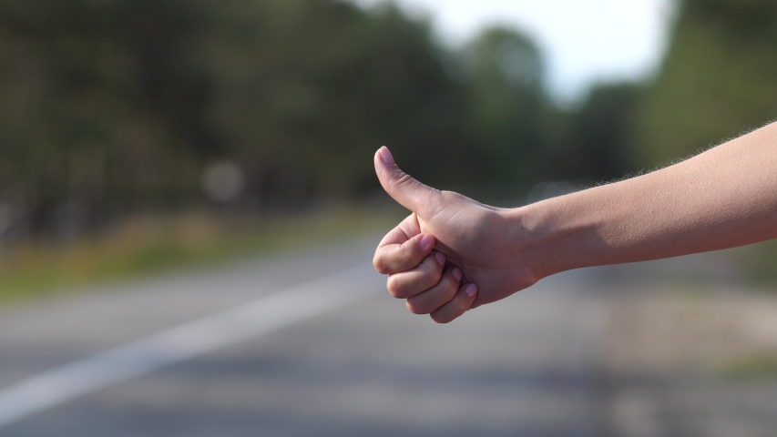 Close-up of the thumb of a female finger. The girl is trying to stop the car on the road.   Shutterstock HD Video #1038911177