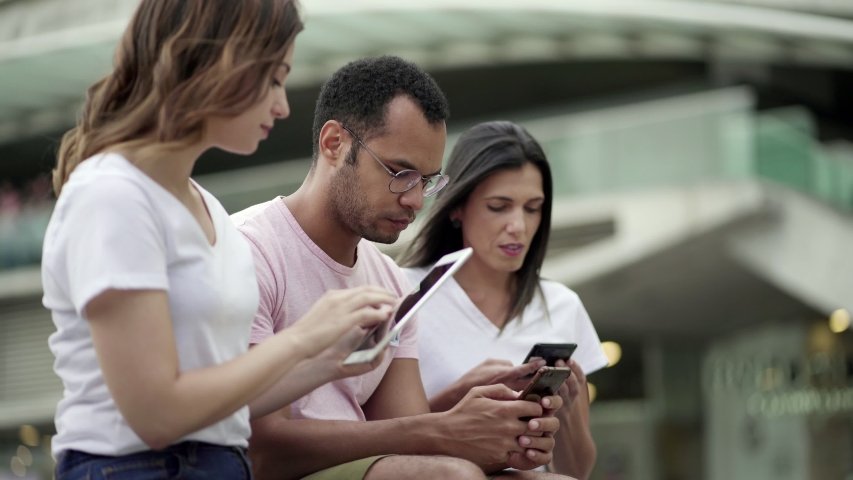 Group of young people using devices on street. Calm friends sitting with smartphones and tablet and talking. Communication and technology concept | Shutterstock HD Video #1038917537