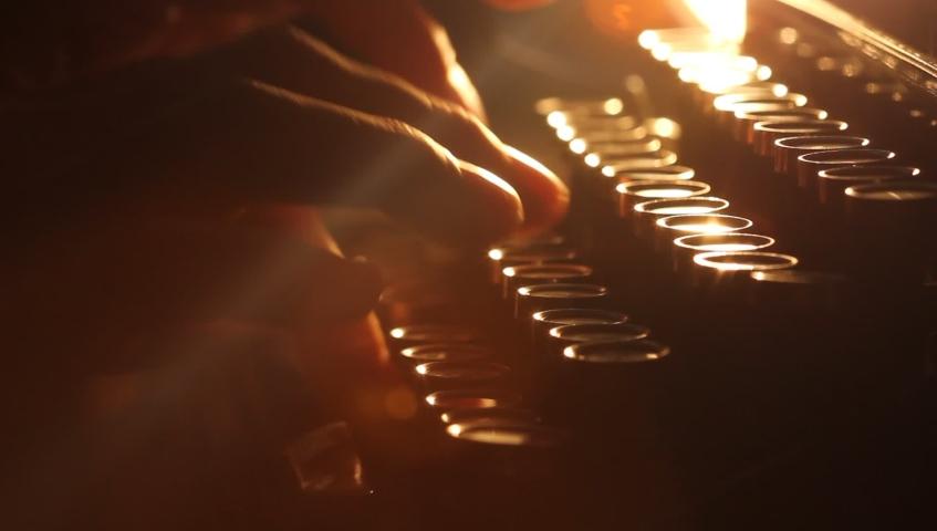 Close up shot of man typing on old vintage retro typewriter; backlit; news, media or communication concept | Shutterstock HD Video #1038918527