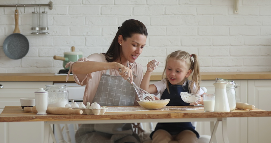 Happy family young mom and cute little child daughter beating dough mixing eggs and flour in modern kitchen, small kid girl helping mum cooking together preparing cake or cookies on mothers day | Shutterstock HD Video #1038952457